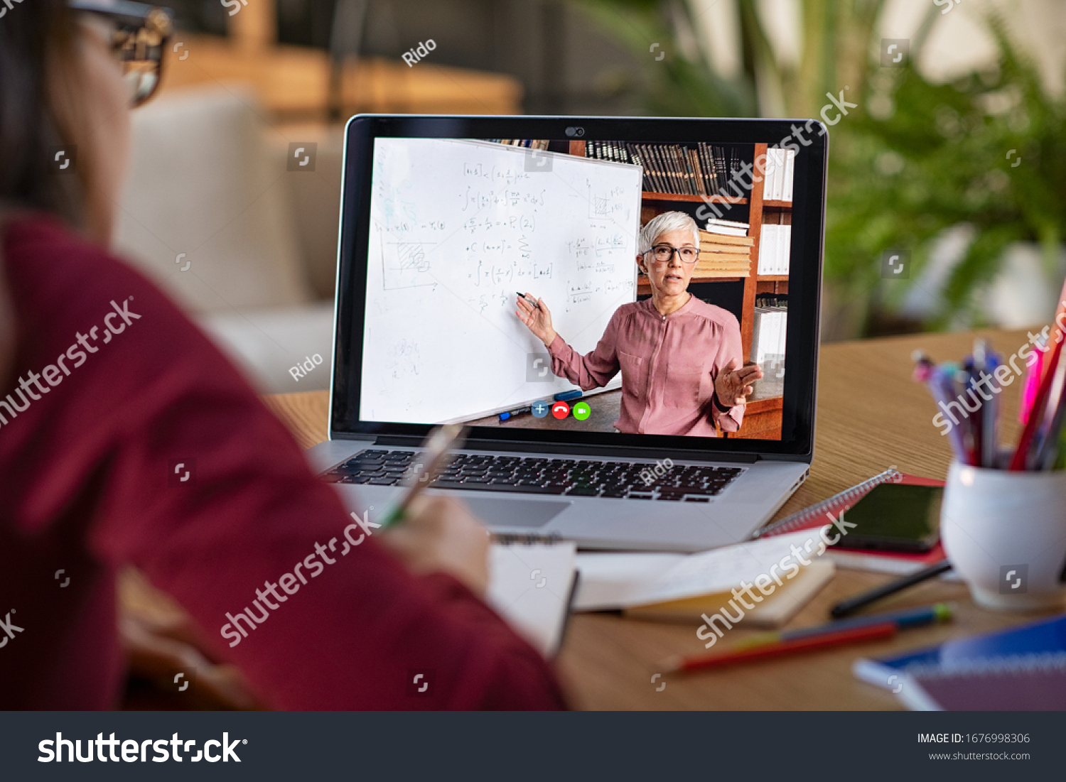 Young student watching lesson online and studying from home. Young woman taking notes while looking at computer screen following professor doing math on video call. Girl studying from home on pc. #1676998306
