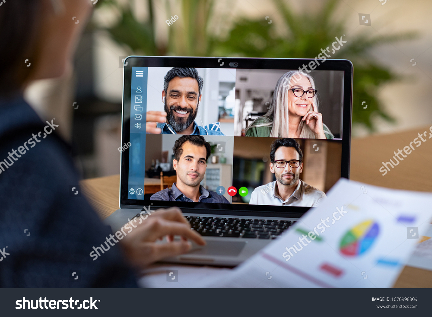 Back view of business woman talking to her colleagues about plan in video conference. Multiethnic business team using laptop for a online meeting in video call. Group of people smart working from home #1676998309