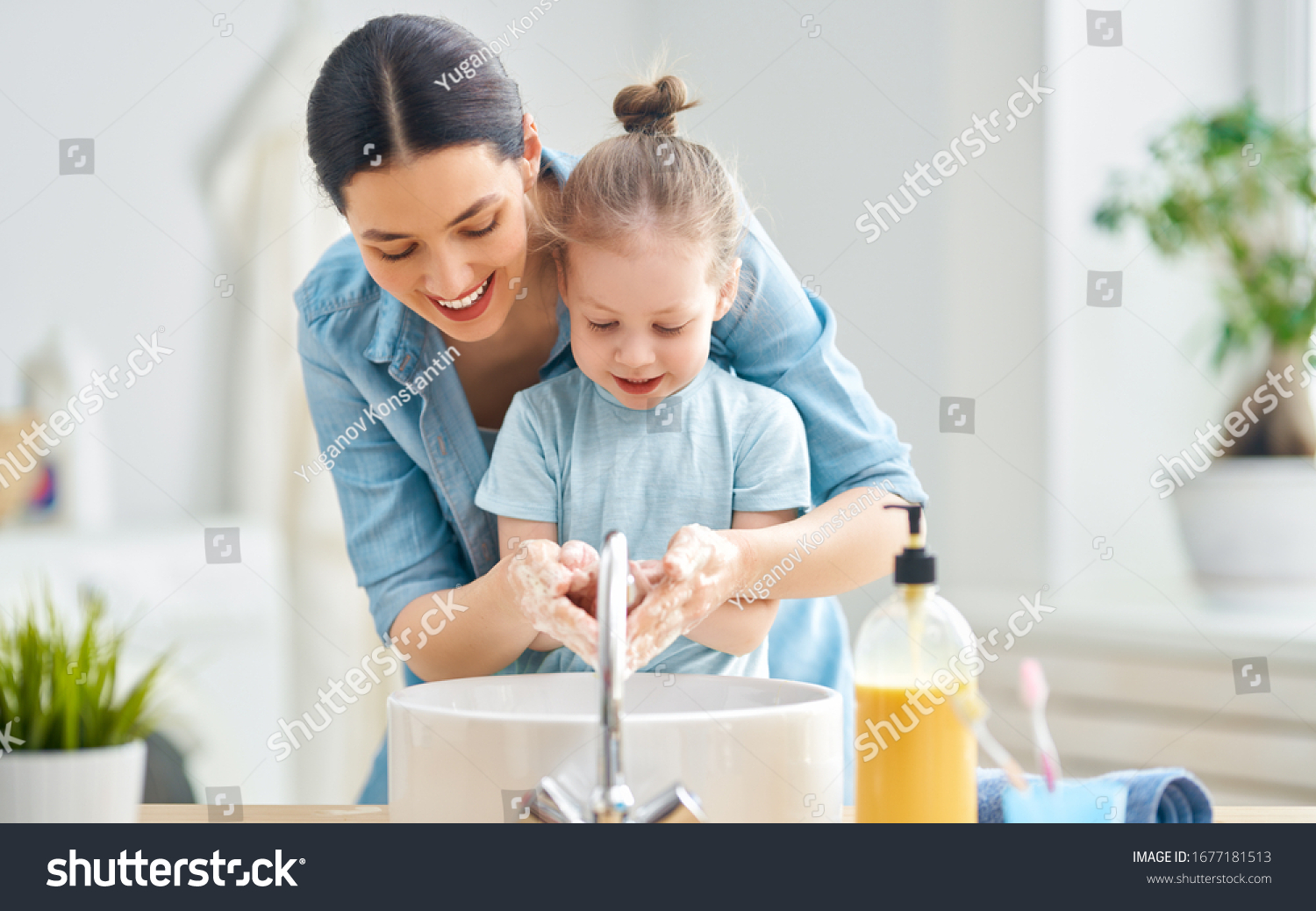 A cute little girl and her mother are washing their hands. Protection against infections and viruses.                                #1677181513