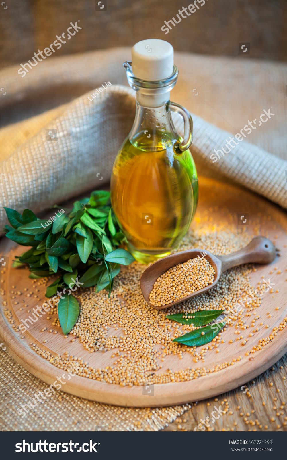 mustard oil in a vessel with seeds on a wooden background