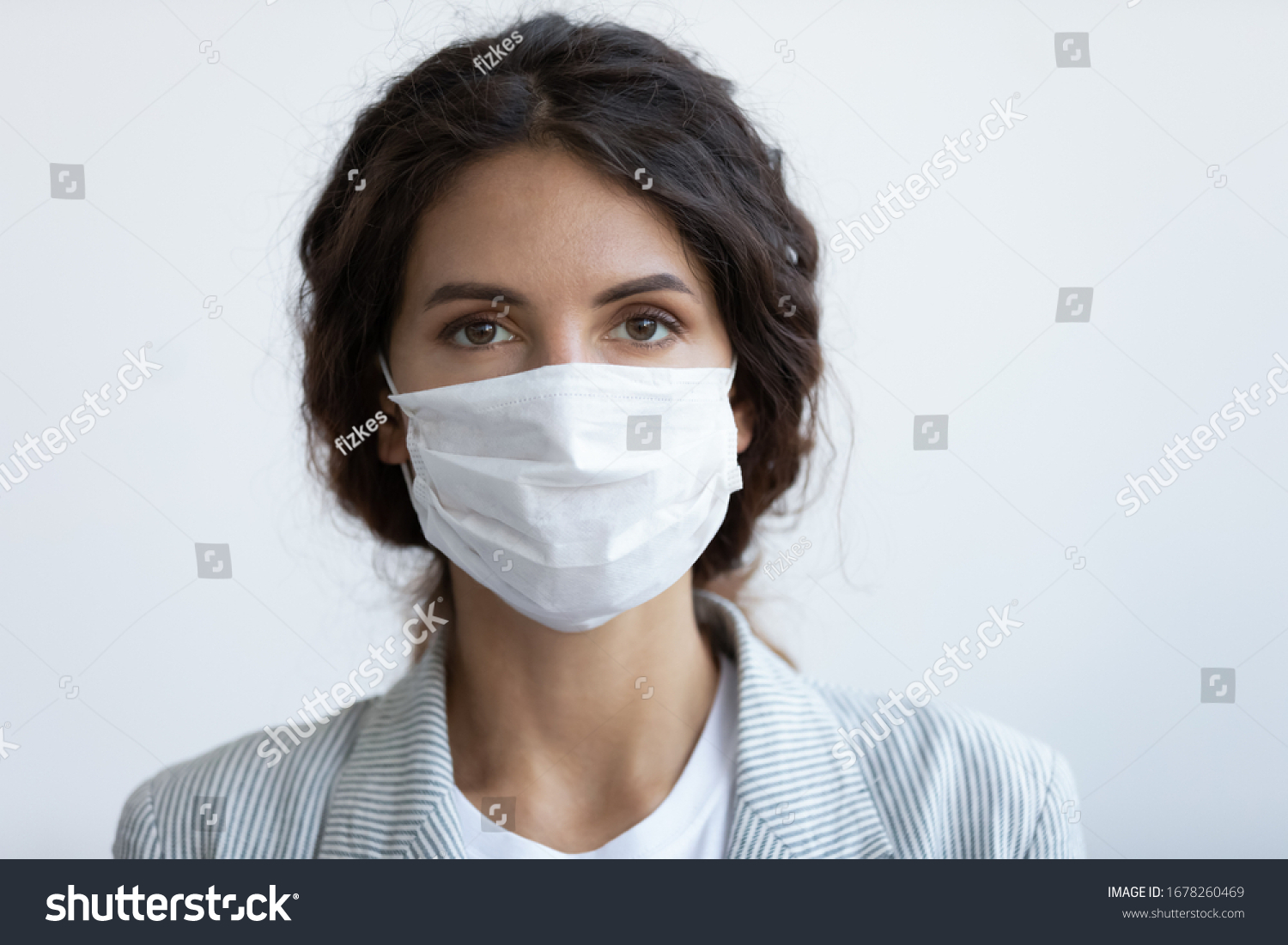 Head shot portrait attractive woman looking at camera wear medical or surgical blue colour face mask protecting from COVID19 or corona virus. Personal care during pandemic infectious disease outbreak #1678260469