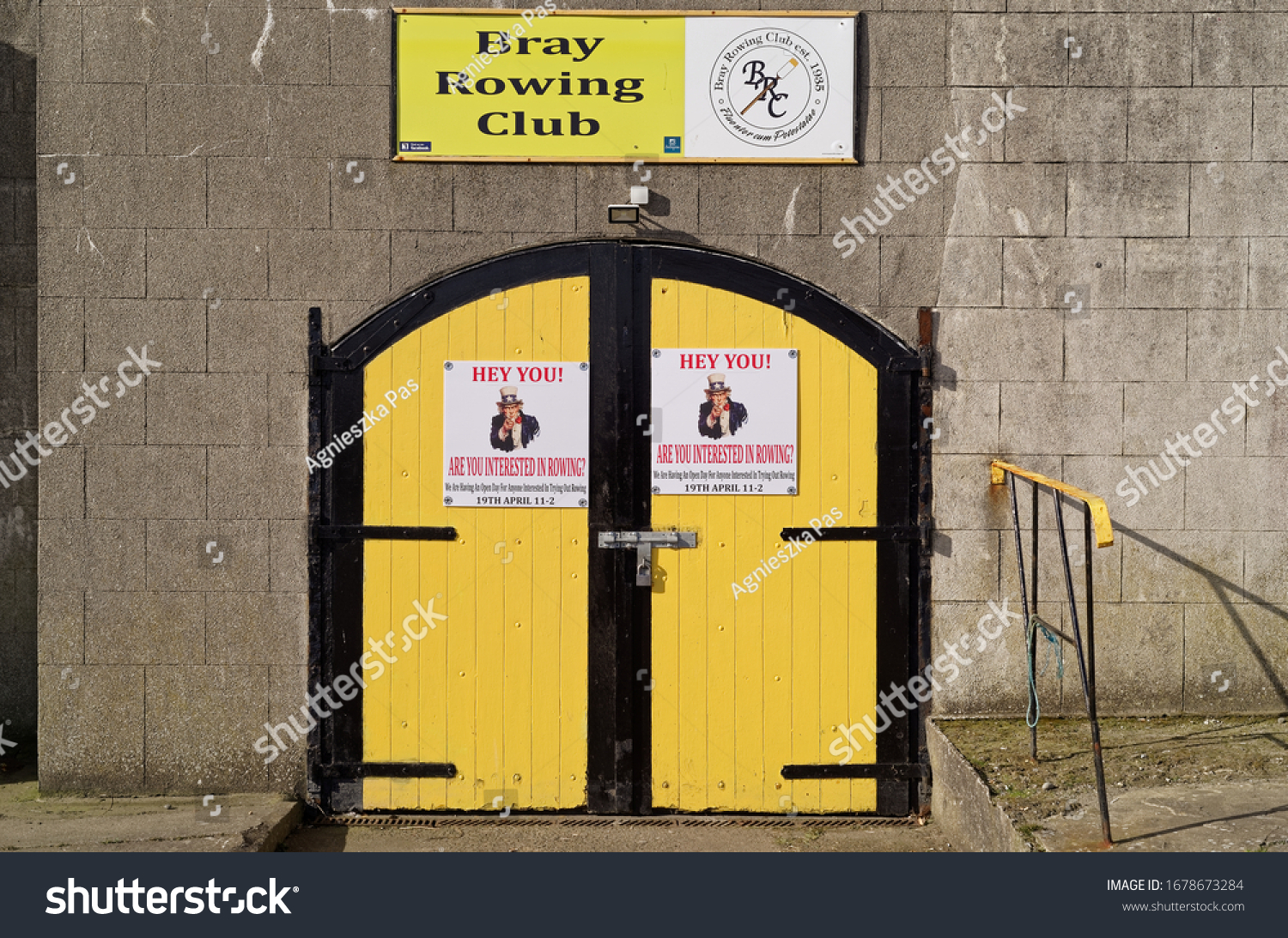 BRAY, CO. WICKLOW, IRELAND - MARCH 16, 2020: An entrance to the Bray Rowing Club in Bray town. Closed yellow door with posters inviting to an open day in the club. Architectural pattern. Symmetry.