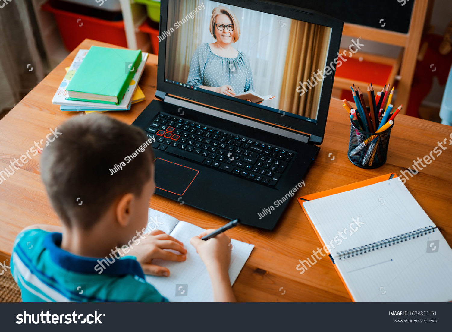 Distance learning online education. A schoolboy boy studies at home and does school homework. A home distance learning. #1678820161