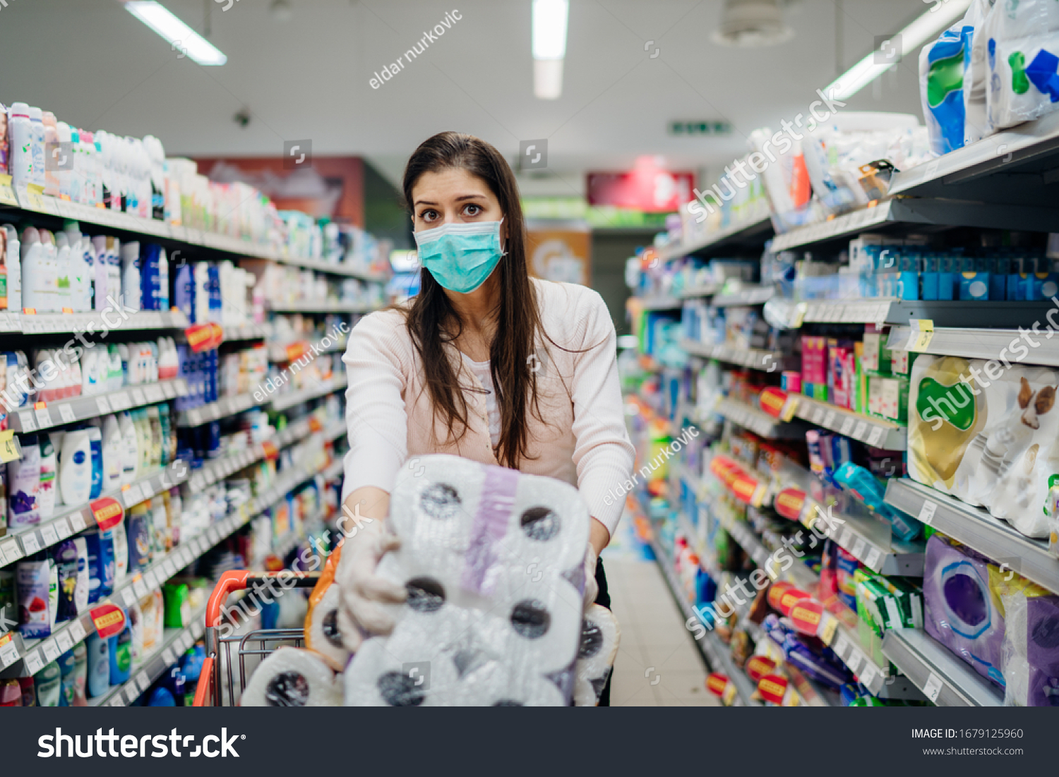 Woman shopper with mask and gloves panic buying and hoarding toilette paper in supply store.Preparing for pathogen virus pandemic quarantine.Prepper buying bulk cleaning supplies due to Covid-19. #1679125960