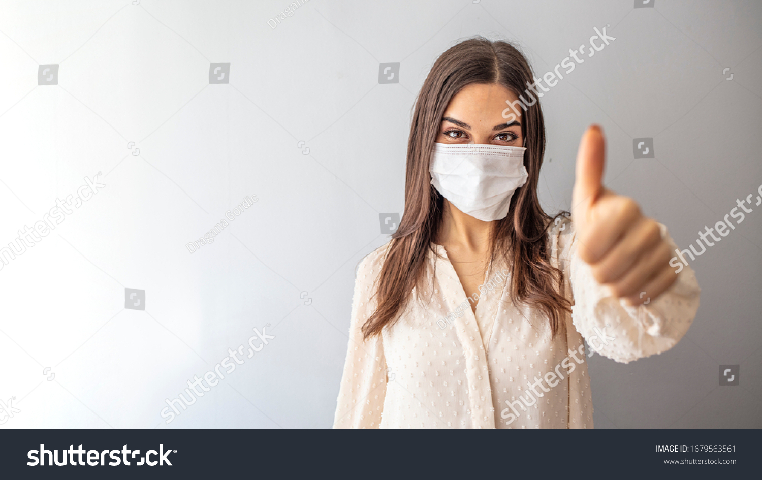 Beautiful caucasian young woman with disposable face mask. Protection versus viruses and infection. Studio portrait, concept with white background. Woman showing thumb up.  #1679563561