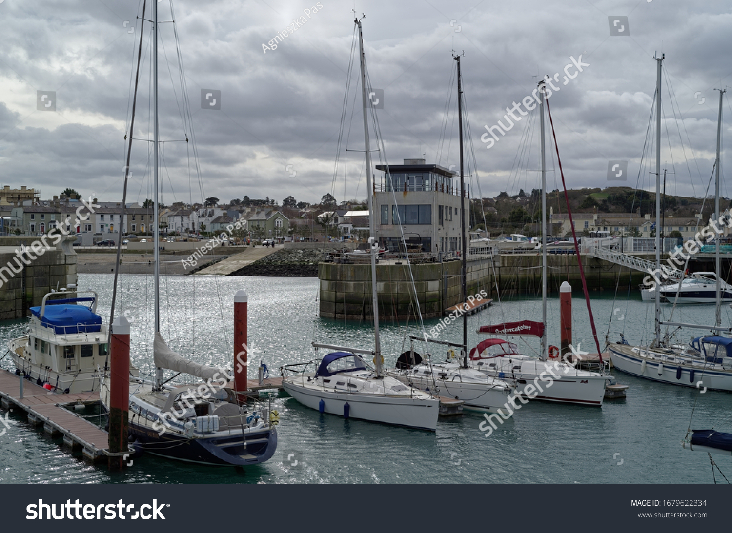 GREYSTONES, CO. WICKLOW, IRELAND - MARCH 16, 2020: Yachts docking at the Greystones Harbour Marina. The Marina and Harbour Master's Office building at the background. Cloudy day.