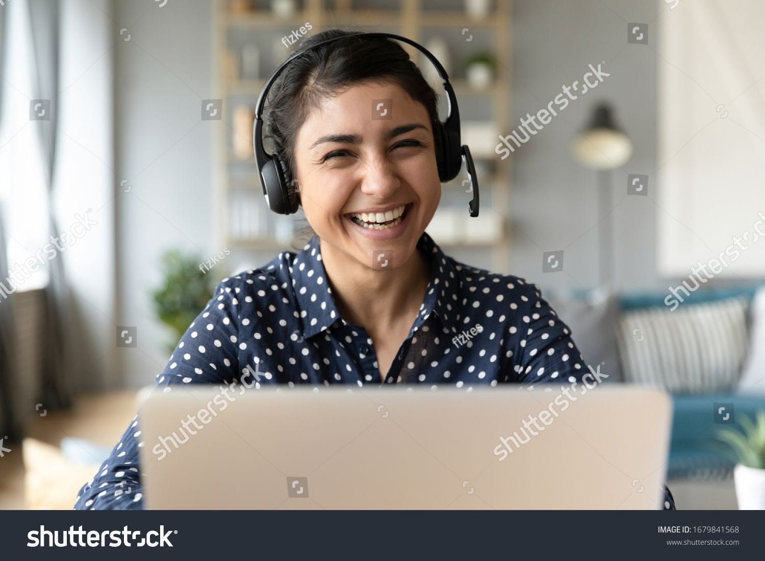 Head shot portrait smiling Indian woman wearing headphones posing for photo at workplace, happy excited female wearing headset looking at camera, sitting at desk with laptop, making video call #1679841568