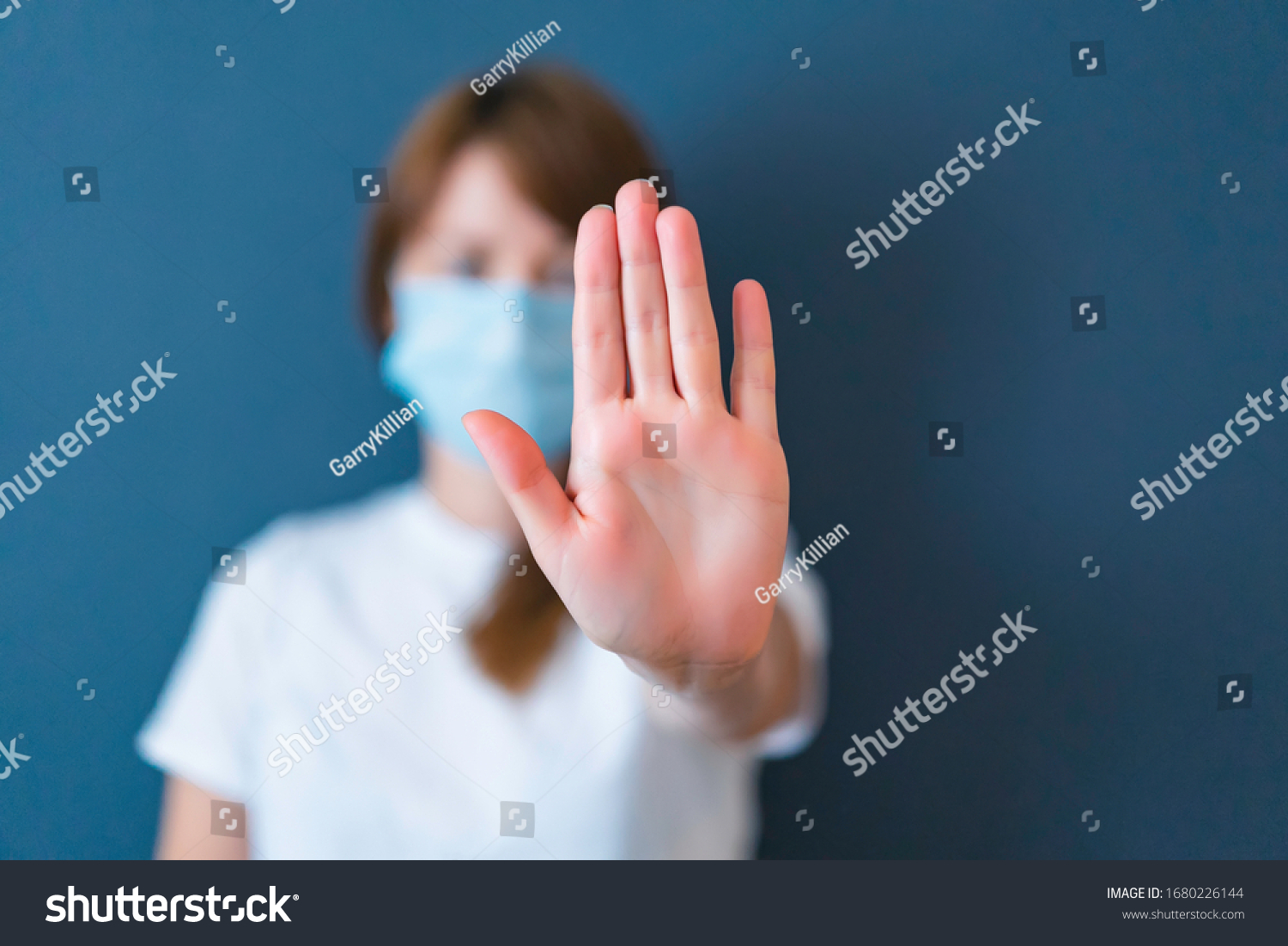 Coronavirus concept. Girl wearing mask for protection from disease and show stop hands gesture for stop corona virus outbreak. Global call to stay home #1680226144