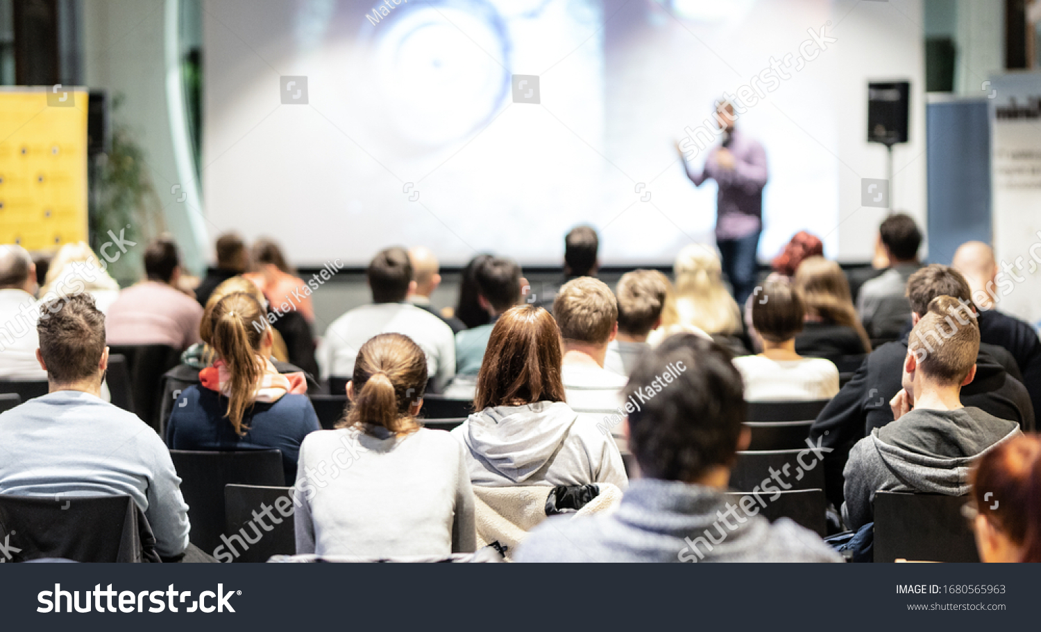 Speaker giving a talk in conference hall at business event. Rear view of unrecognizable people in audience at the conference hall. Business and entrepreneurship concept. #1680565963