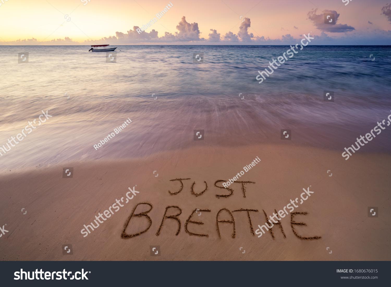 Handwritten Just breathe on sandy beach at sunset,relax and summer concept,Dominican republic beach. #1680676015