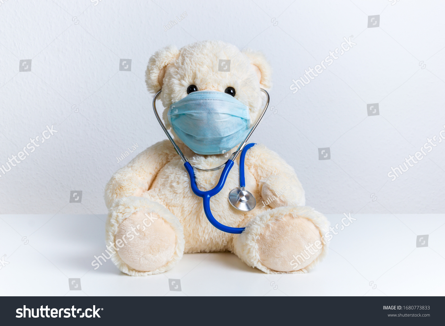Cute teddy bear doctor with protective medical mask and stethoscope. Concept of pediatric treatment of illness, hygiene, epidemic and virus protection for child patient. Fluffy toy on white background #1680773833