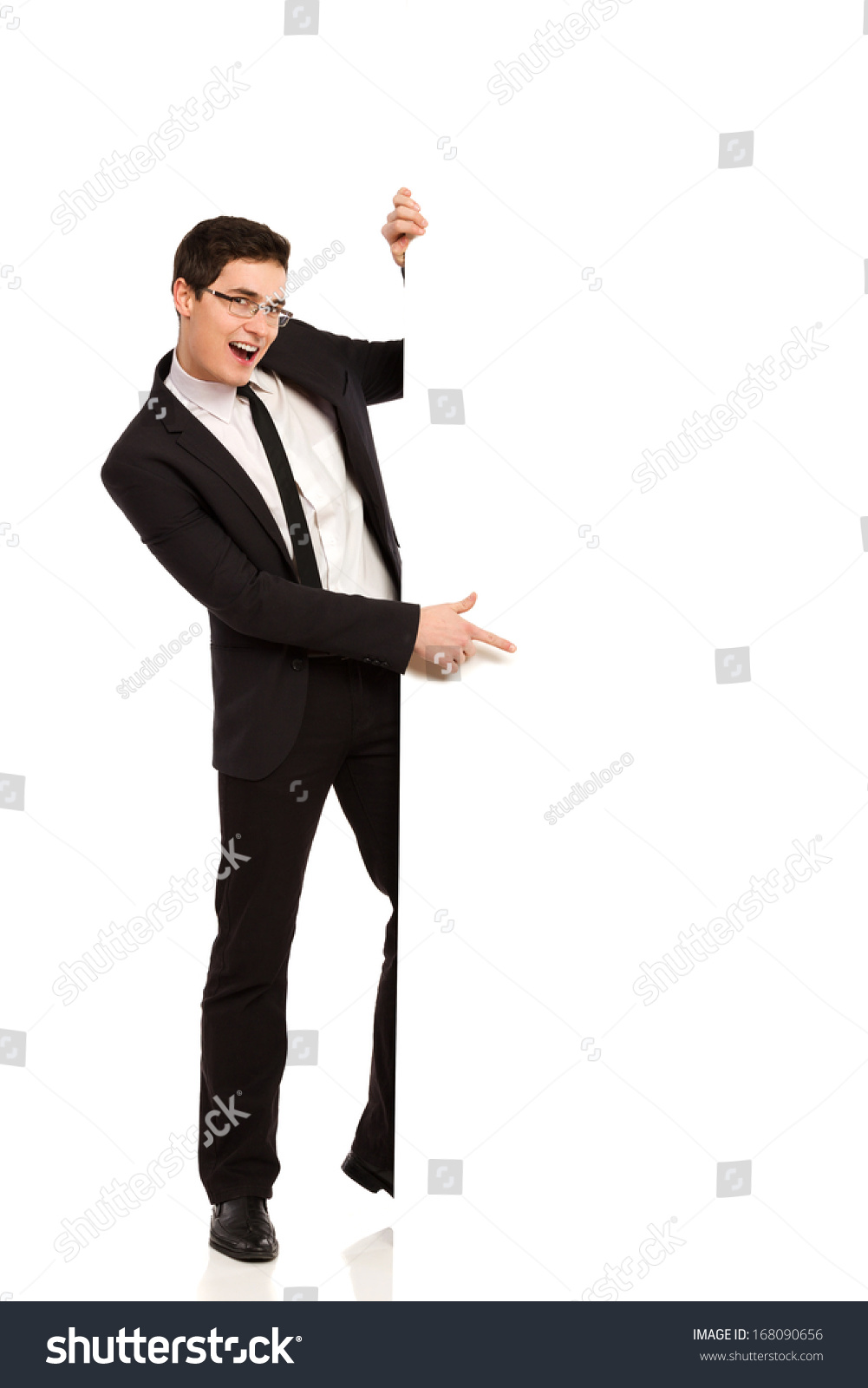 f8aaa37324 Young man in black suit pointing at the banner. Full length studio shot  isolated on.