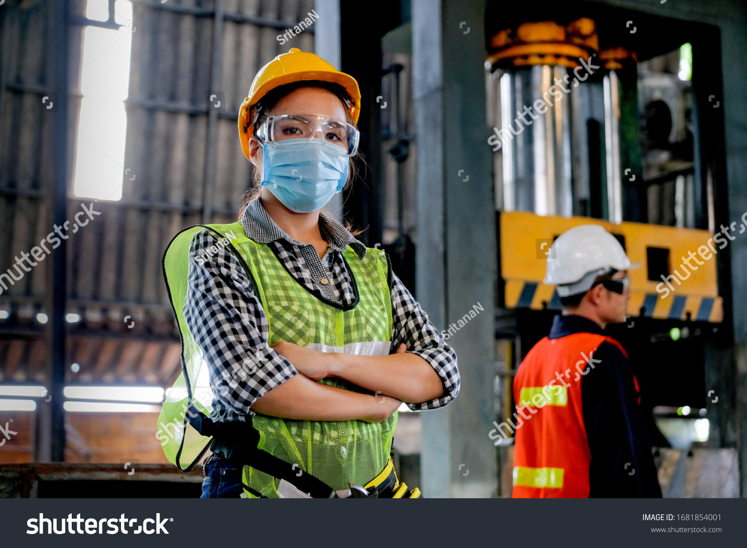 Factory woman worker or technician with hygienic mask stand with confident action with her co-worker engineer in workplace during concern about covid pandemic in people affect industrial business. #1681854001