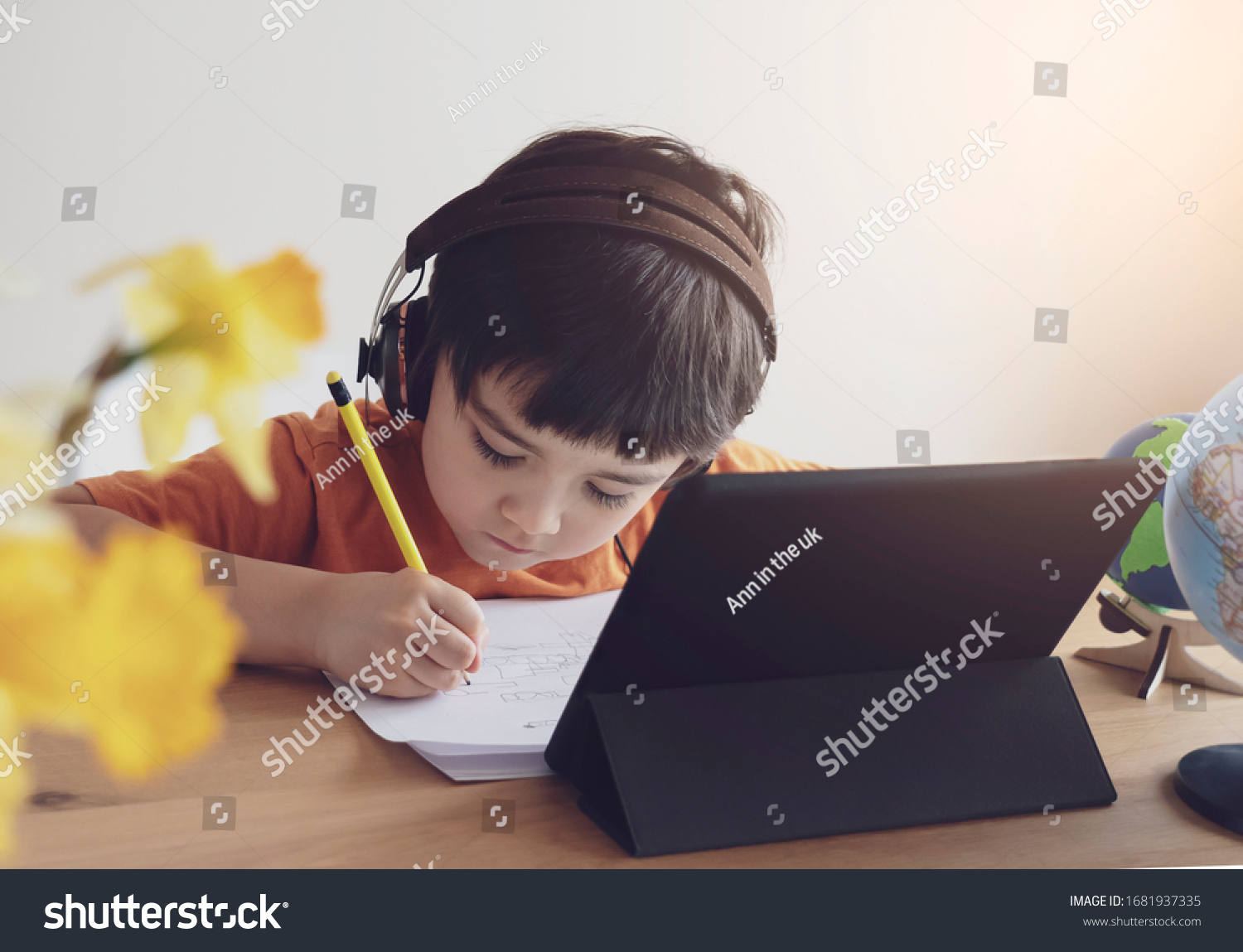 Kid self isolation using tablet for his homework,Child doing using digital tablet searching information on internet during covid 19 lock down,Home schooling,Social Distance,E-learning online education #1681937335