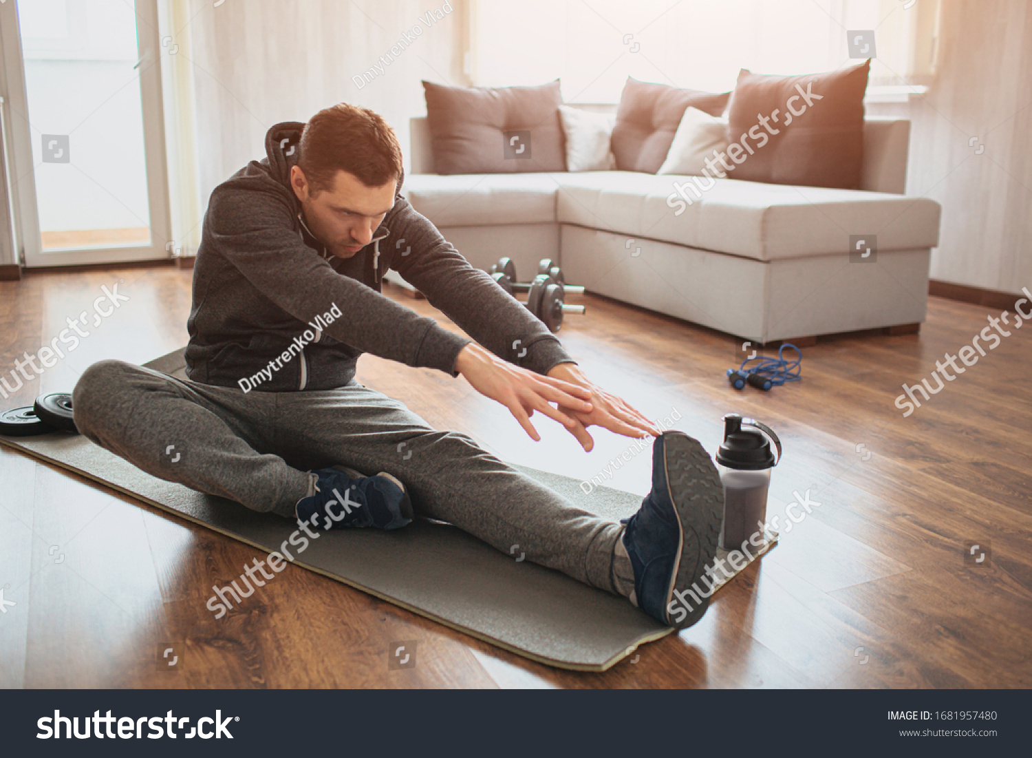 Young ordinary man go in for sport at home. Freshman or beginner stretching with tow hands to one leg. Excercising alone in empty apartment. Try to keep fit and stay healthy with good body #1681957480