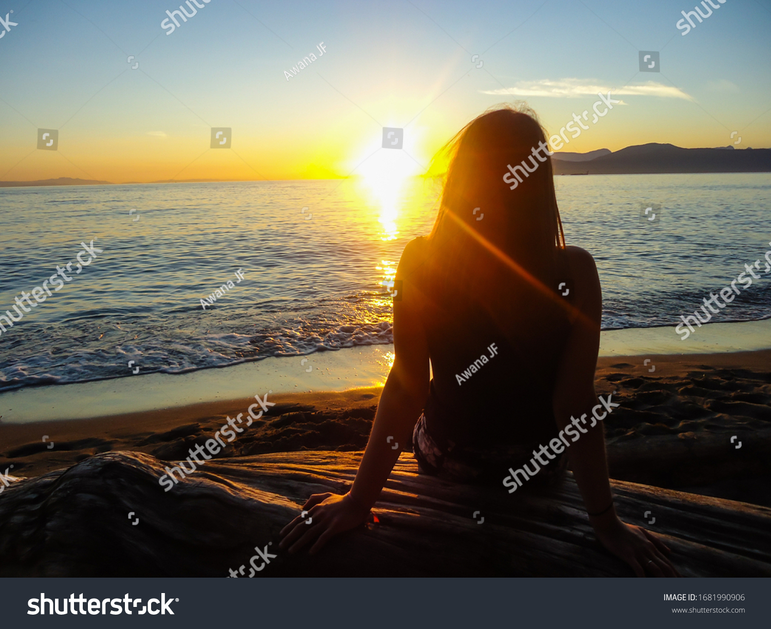 Back view of a young woman sitting on a beach watching a beautiful sunset in Vancouver