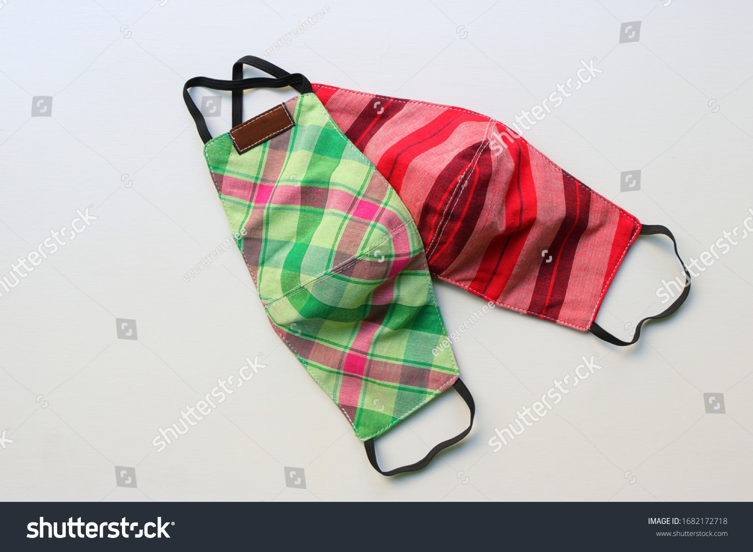 Two handmade face masks made from plaid cloth placed on wooden table, washable and reusable, can be used during shortage of surgical mask due to coronavirus pandemic