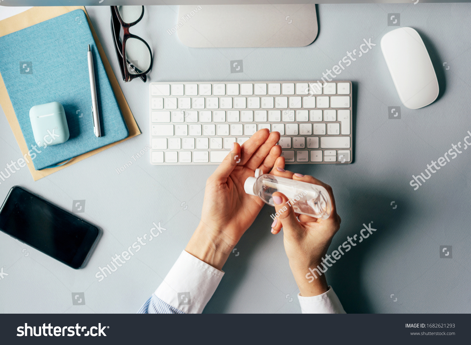 Close-up of hands using antiseptic gel to disinfect hands over a work desk in an office. Preventive measures during the period of epidemic and social exclusion. #1682621293