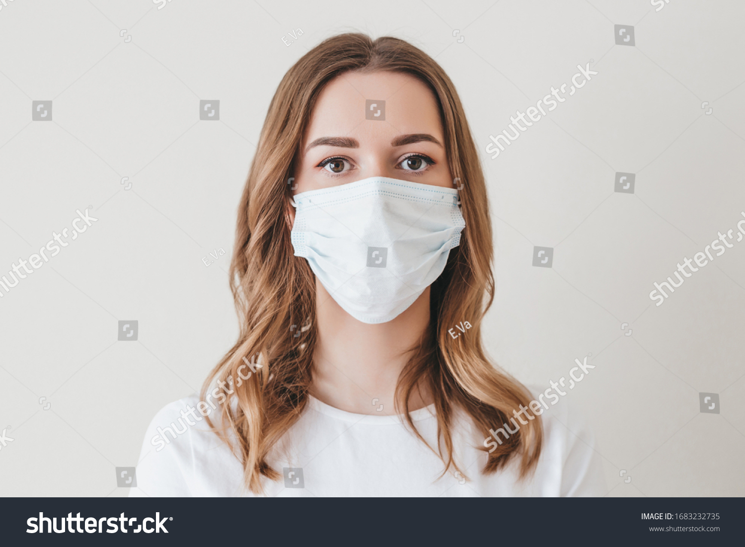 Portrait of a young girl in a medical mask isolated on a white wall background. Young woman patient, copy space #1683232735