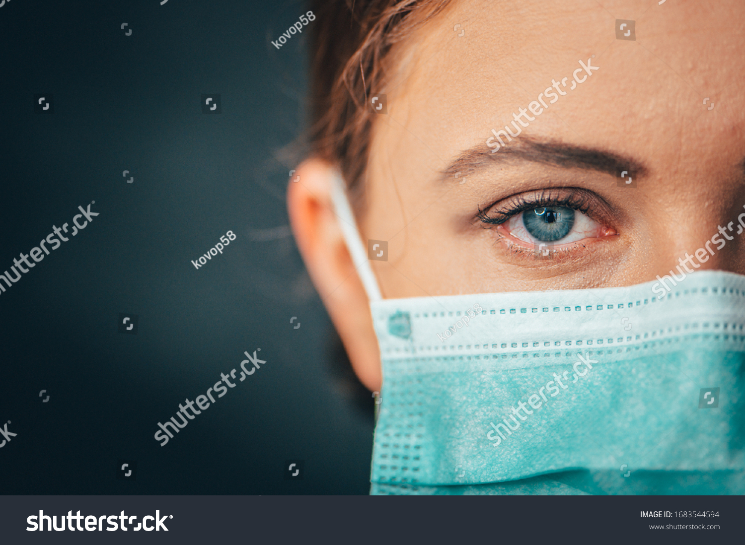 Close up portrait photo, Eye of Yong Female Doctor. Protection against contagious disease, coronavirus, hygienic face surgical medical mask to prevent infection. Black background #1683544594