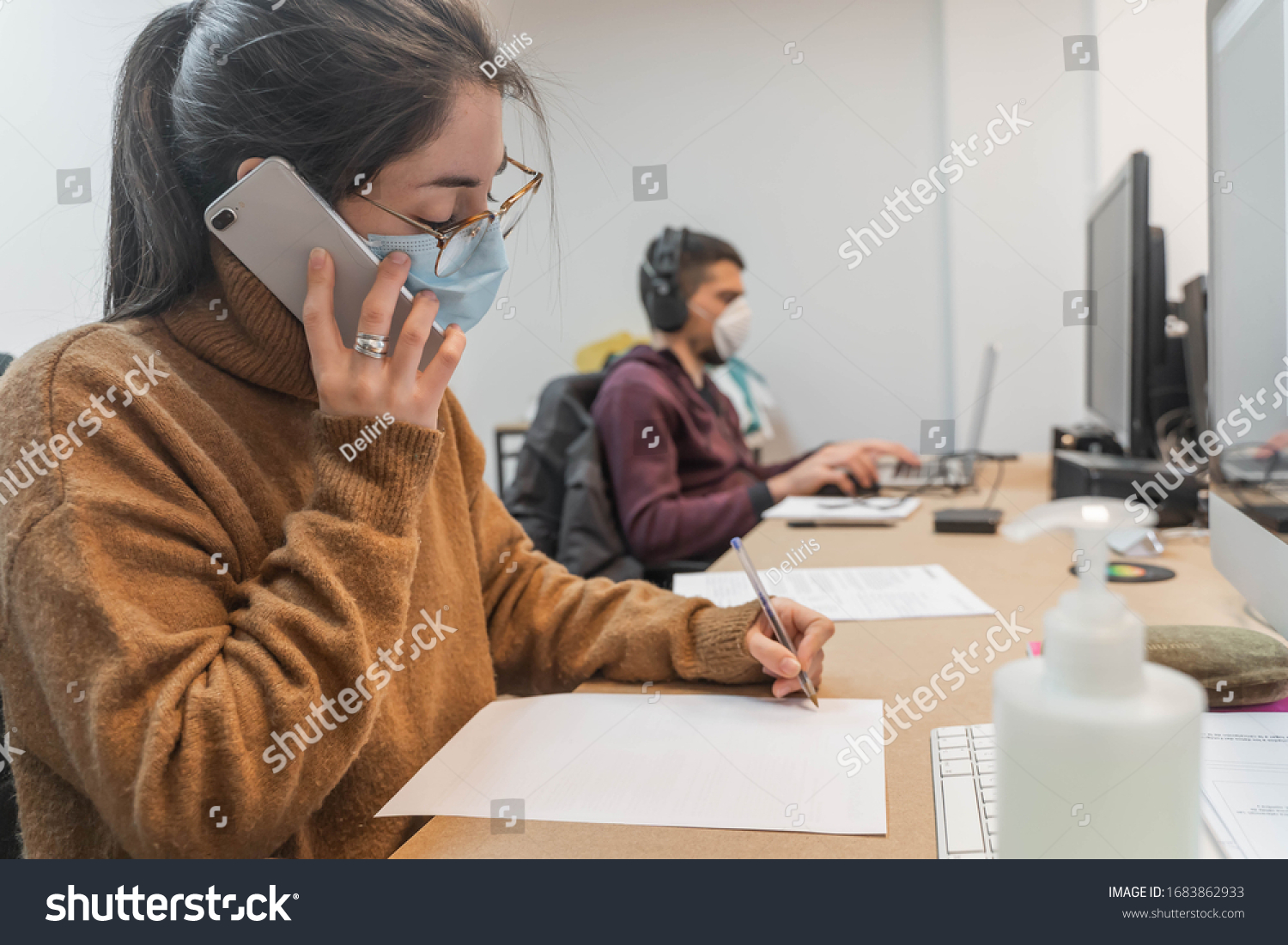 Coronavirus. Business workers working from home wearing protective mask. Small company in quarantine for coronavirus working from home with sanitizer gel. Small company concept. #1683862933