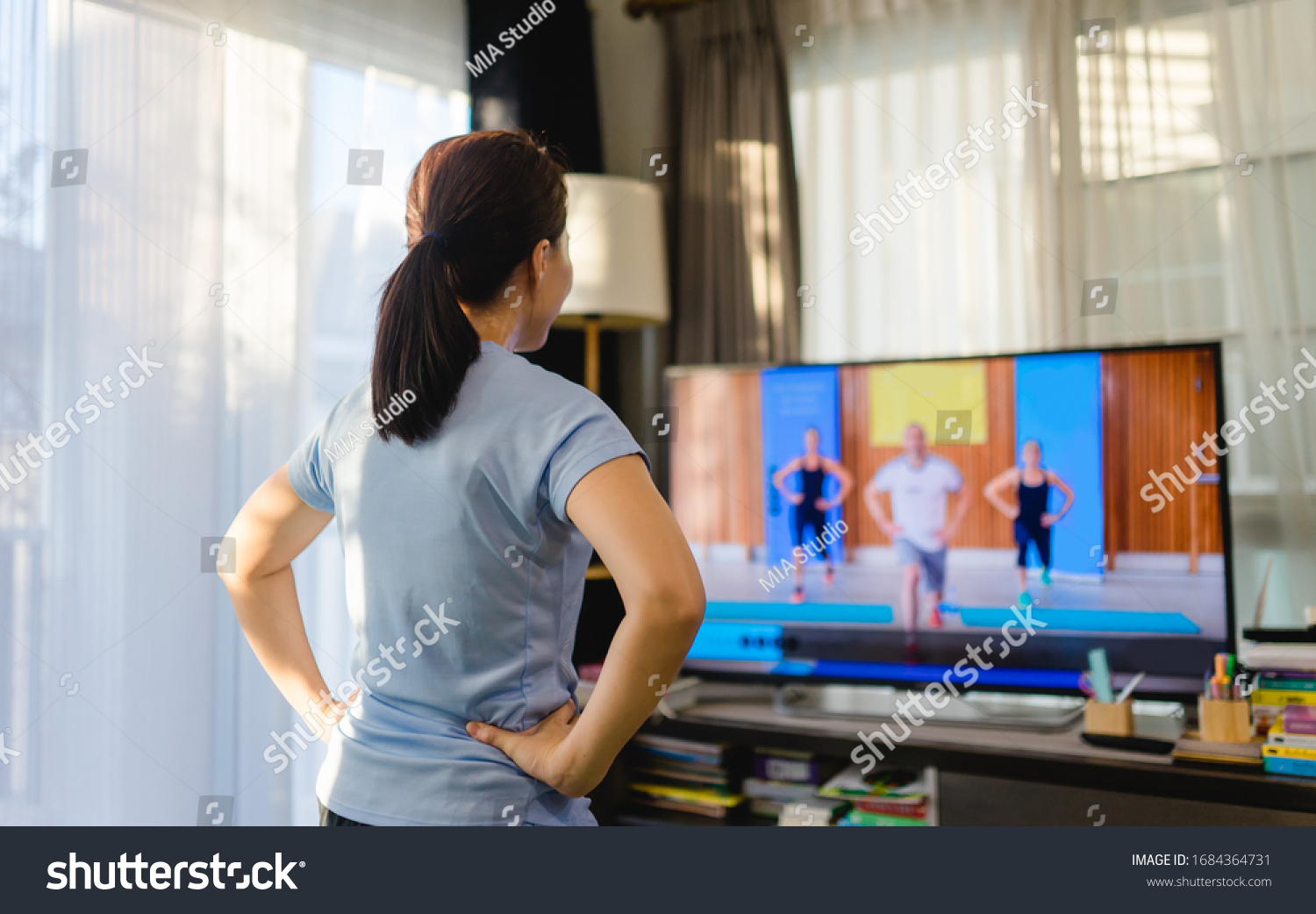 Video streaming Stay home.home fitness workout class live streaming online.Asian woman doing strength training cardio aerobic dance exercises watching videos on a smart tv in the living room at home. #1684364731