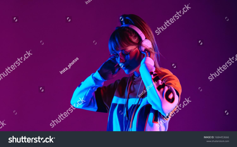 Calm girl wear stylish glasses headphones listen music at purple background. #1684453666