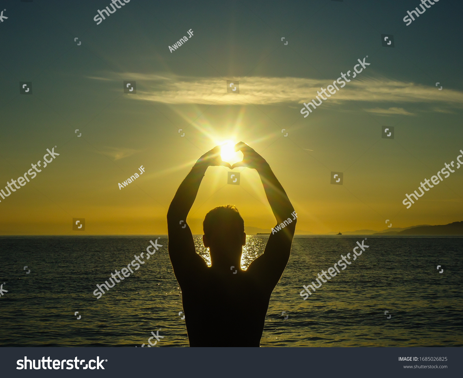 Silhouette of a man standing in front of the pacific ocean forming a heart with his hands during a sunset on the university of british columbia campus beach