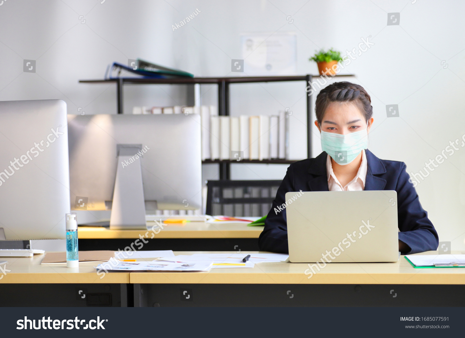 Female employee wearing medical facial mask working alone as of social distancing policy in the business office during new normal change after coronavirus or post covid-19 outbreak pandemic situation #1685077591