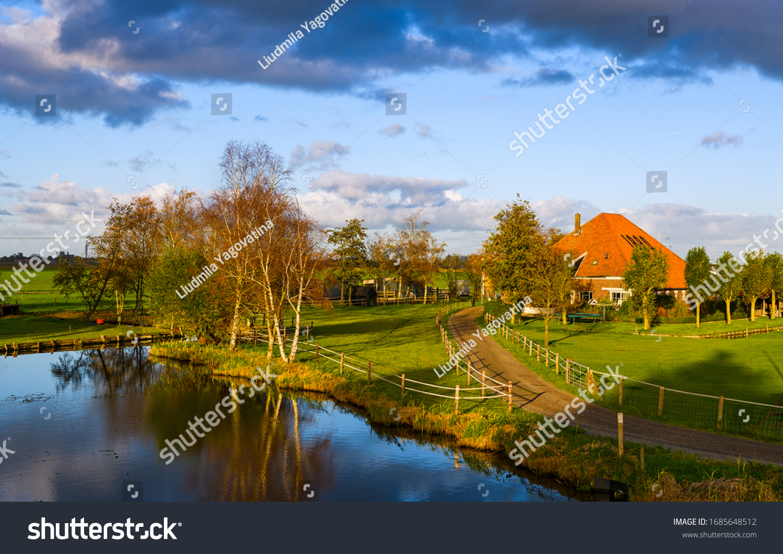 Sunset spring village river landscape. Farm house river scene. River farm house in spring. Farm house river water reflection #1685648512