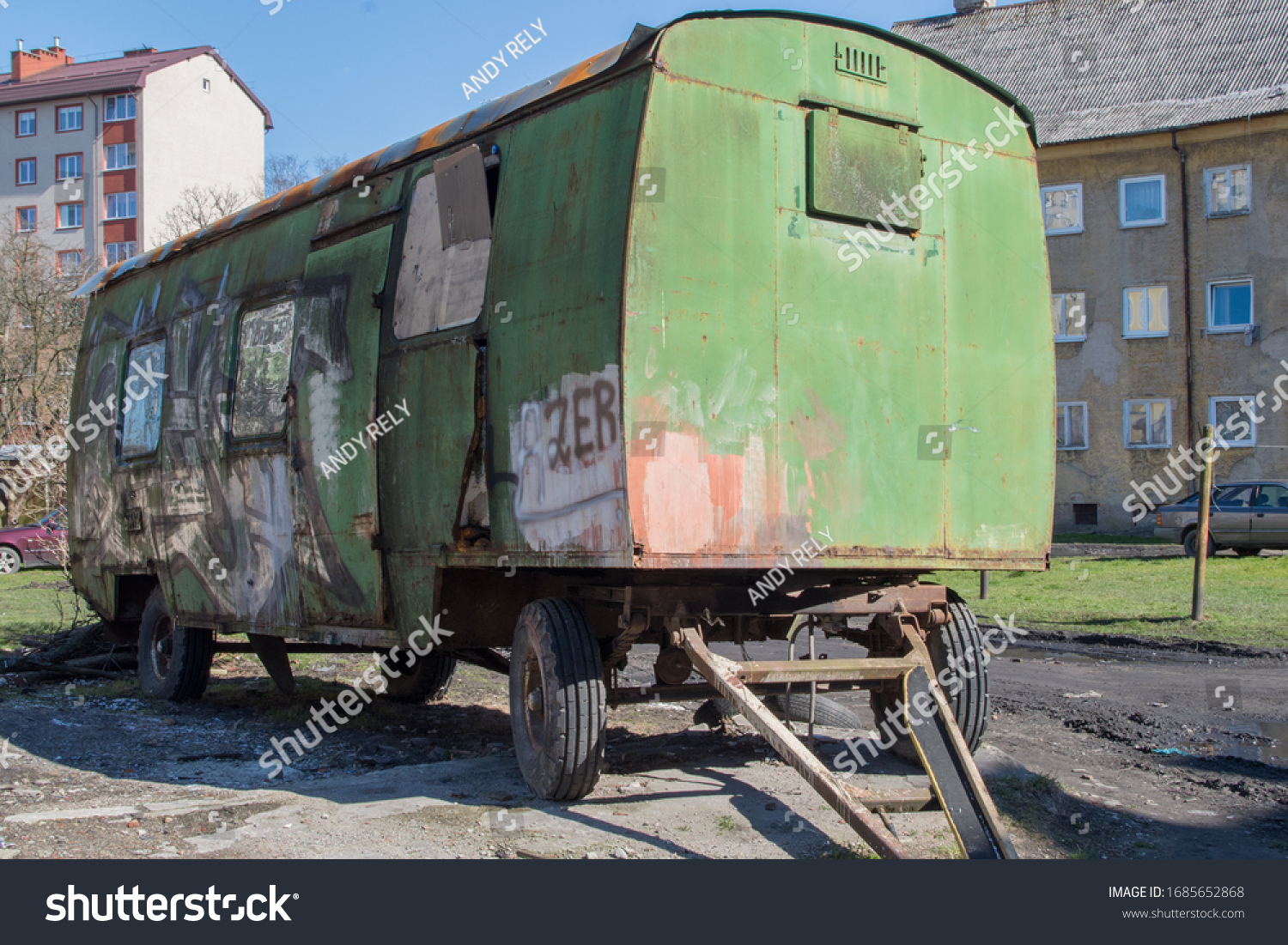 KALININGRAD, RUSSIA – 22 MARCH, 2020:  Green, battered, dented long metal trailer on wheels with closed windows and traces of graffitit, standing in a courtyard surrounded by beige apartment buildings