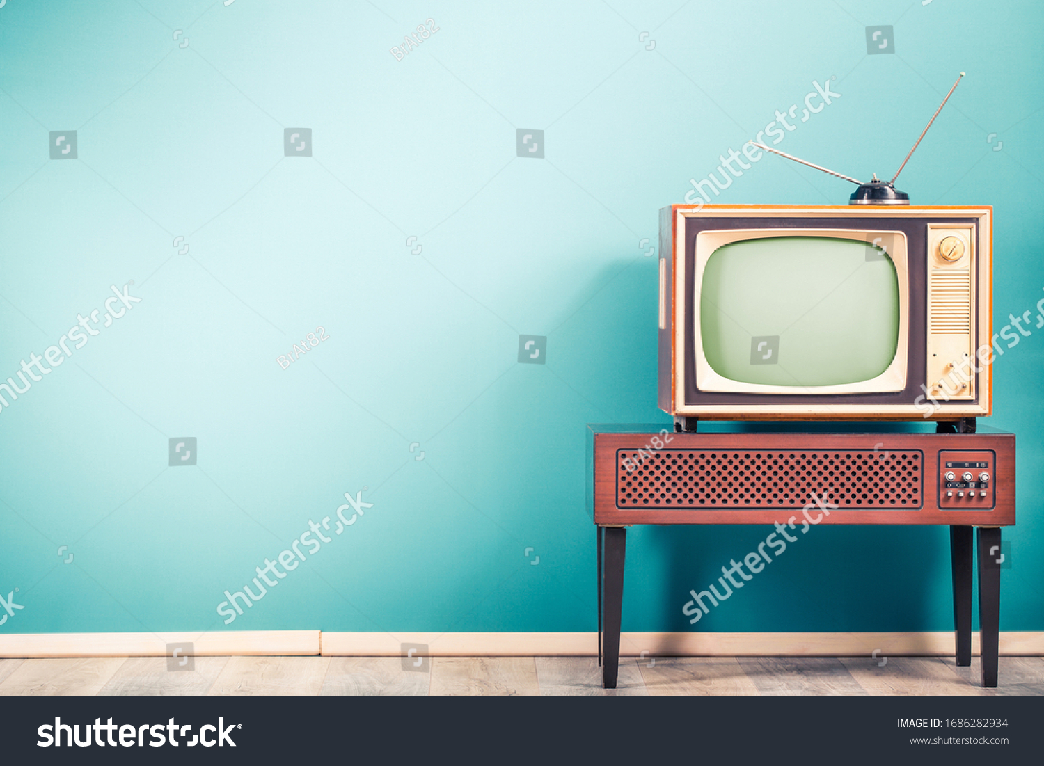 Retro old outdated classic television receiver with TV antenna from circa 60s of XX century on wooden stand with amplifier front gradient mint blue wall background. Vintage style filtered photo #1686282934