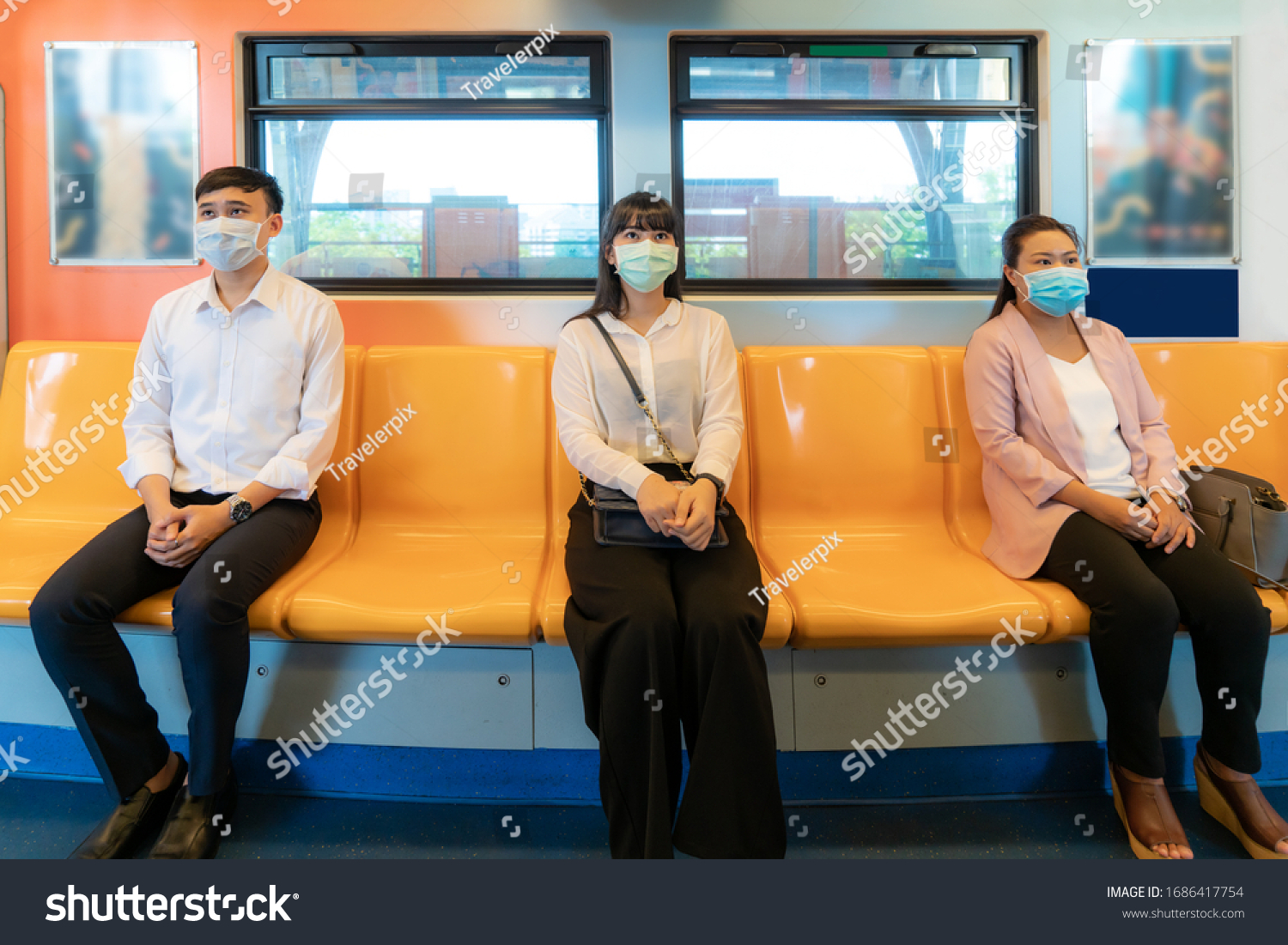 Three Asian people wearing mask sitting in subway distance for one seat from other people keep distance protect from COVID-19 viruses and people social distancing  for infection risk   #1686417754