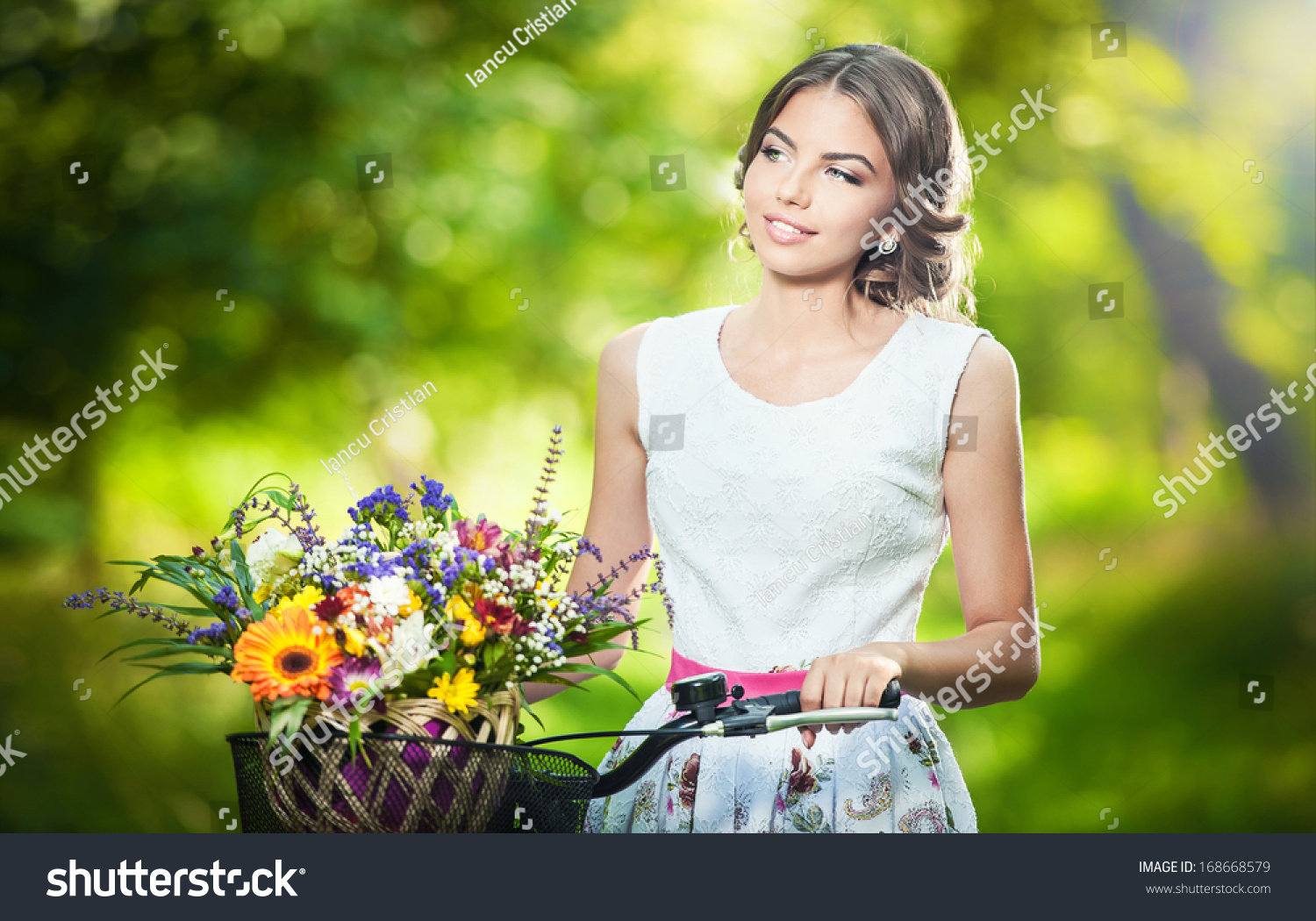Royalty free beautiful girl wearing a nice white 168668579 stock beautiful girl wearing a nice white dress having fun in park with bicycle carrying a beautiful basket full of flowers vintage scenery izmirmasajfo