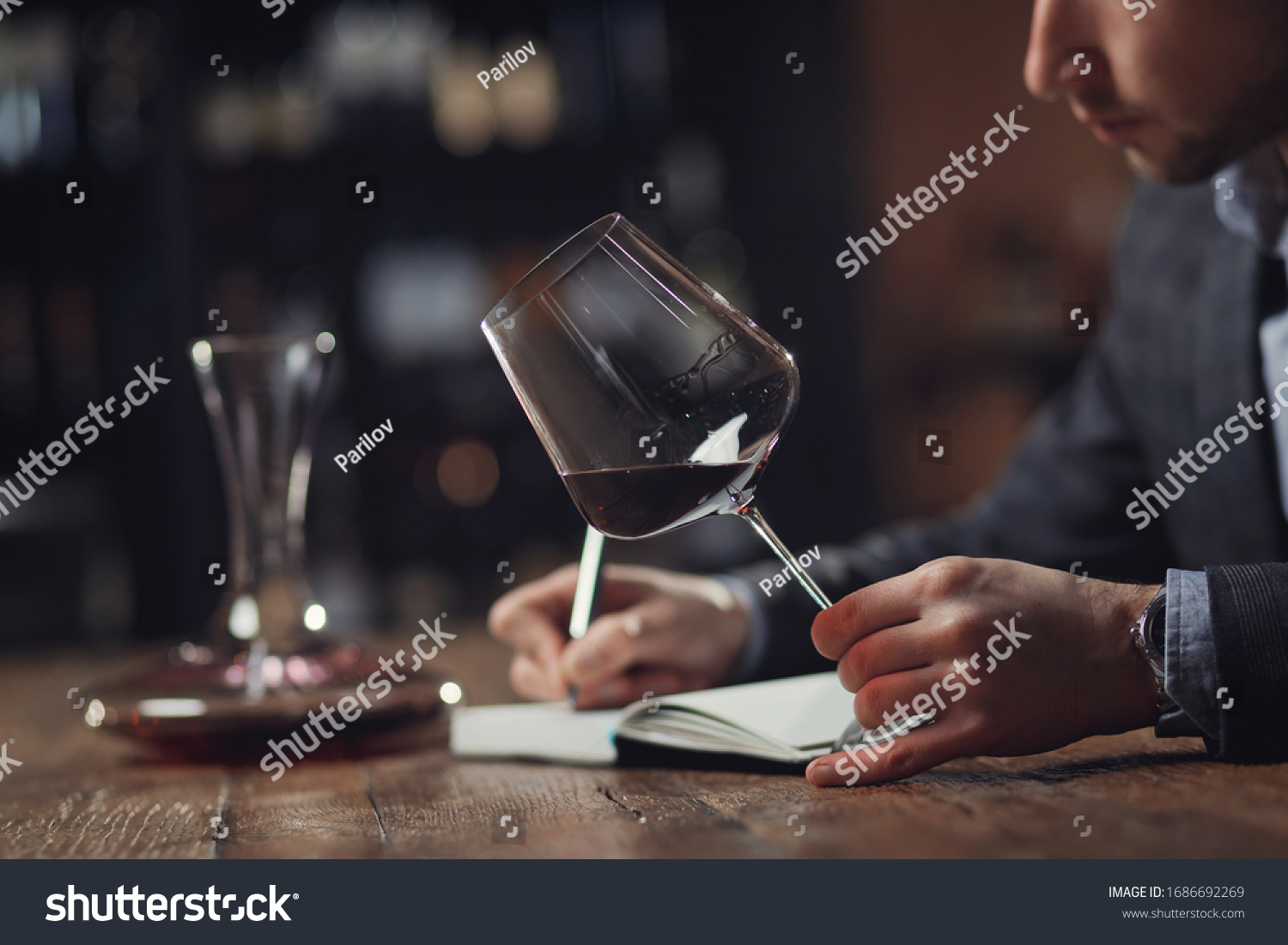 Sommeliers male hold glass red wine tasting and making notes degustation card. #1686692269