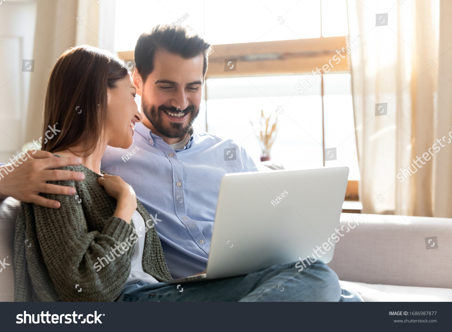Head shot smiling young woman watching comedian movie or funny videos on computer with loving husband at home. Happy married couple spending free leisure weekend holiday time with laptop indoors. #1686987877