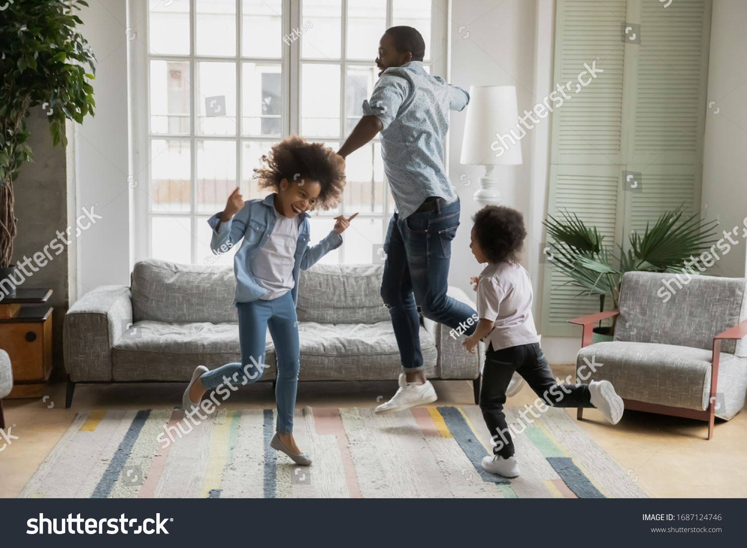 Active african funny dad little son and crazy daughter heavy metal or rock and roll lovers dancing in cozy living room relish life fooling around listening cool music scream with joy enjoy party hard #1687124746