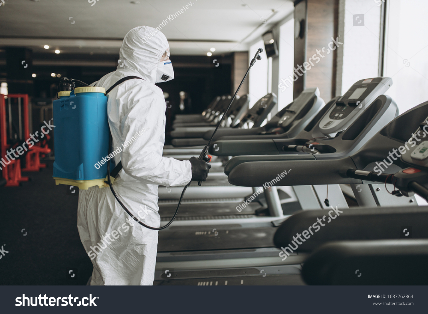 Cleaning and Disinfection in crowded places amid the coronavirus epidemic Gym cleaning and disinfection Infection prevention and control of epidemic. Protective suit and mask and spray bag #1687762864