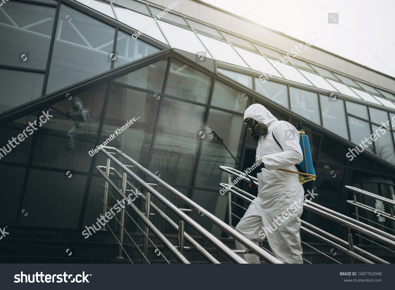 Cleaning and Disinfection at town complex amid the coronavirus epidemic Professional teams for disinfection efforts Infection prevention and control of epidemic Protective suit and mask. #1687762948