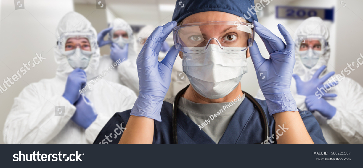 Team of Female and Male Doctors or Nurses Wearing Personal Protective Equiment In Hospital Hallway. #1688225587