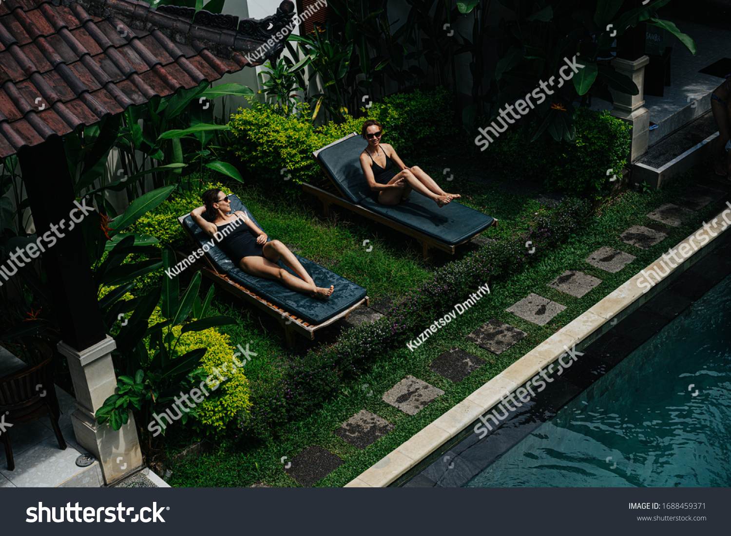 Two women on sun loungers sunbathe in the territory of an asian villa, next to the pool #1688459371