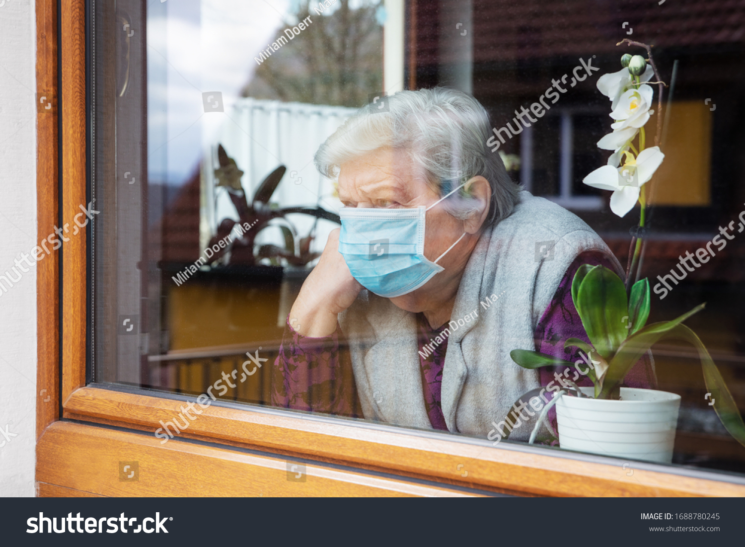 lonely senior woman with surgical mask sitting on a window plane at home, coronavirus and covid-19 provisions #1688780245
