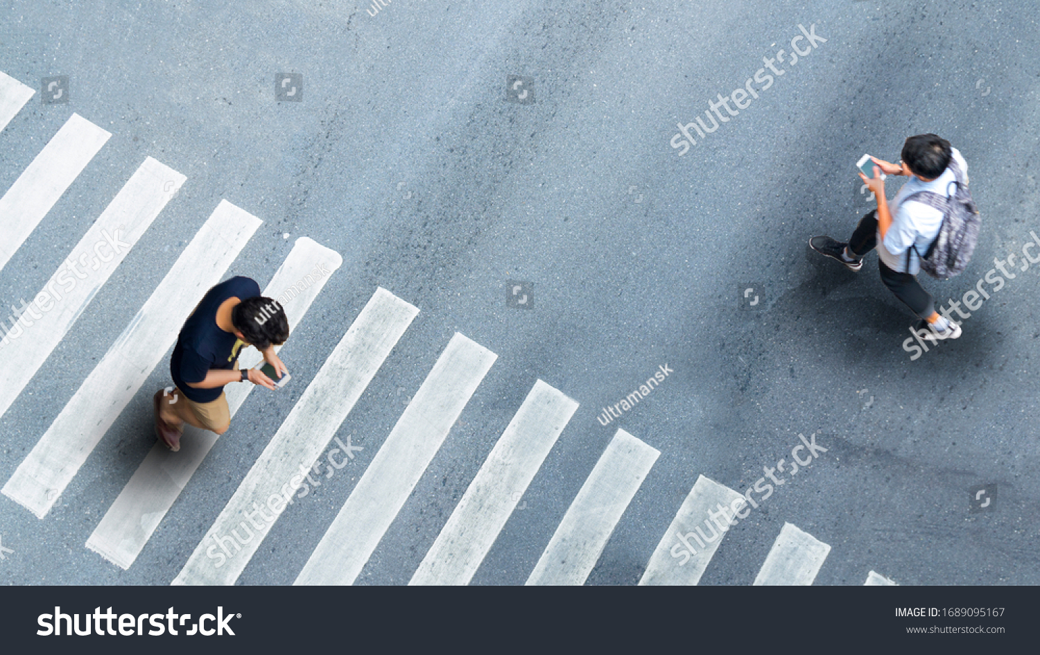 Human life in Social distance. Aerial top view with blur man with smartphone walking converse of other people at pedestrian crosswalk on grey pavement street road with empty space. #1689095167