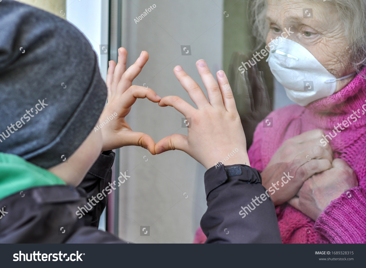 Grandmother mature woman in a respiratory mask communicates with her grandchild through a window. Elderly quarantined, isolated. Coronavirus covid-19. Caring with older people. Family values, love #1689328315