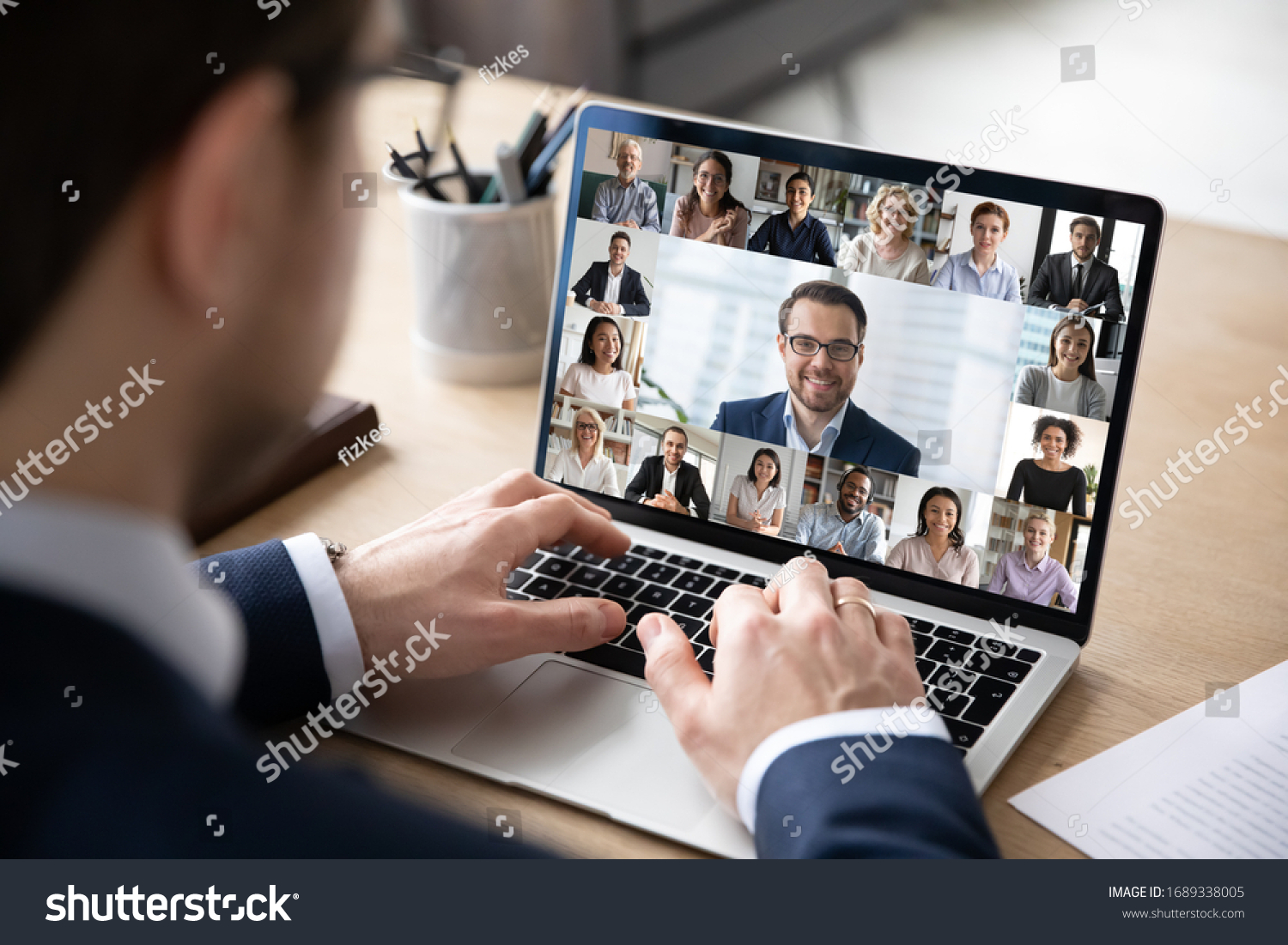 Rear view of businessman speak on web conference with diverse colleagues using laptop Webcam, male employee talk on video call with multiracial coworkers have online meeting briefing from home #1689338005