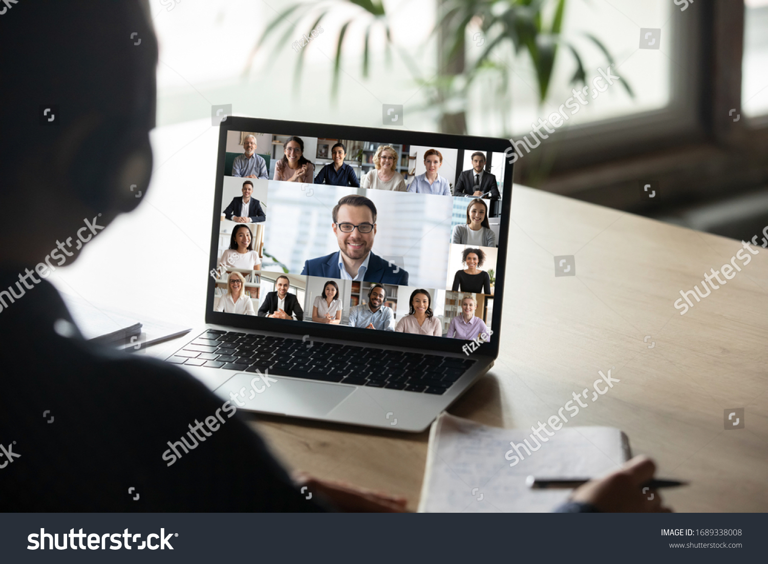 Back view of female employee engaged in team Webcam conference on laptop, have online briefing or consultation from home, woman worker speak talk on group video call with diverse colleagues #1689338008