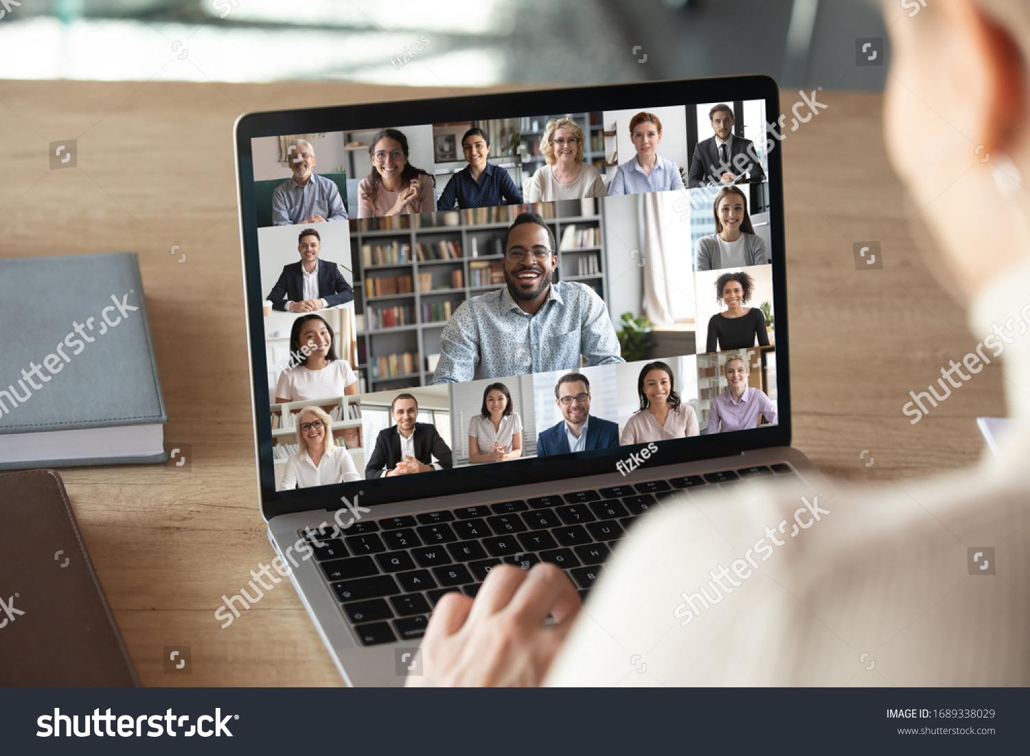 Back view of female employee speak talk on video call with diverse multiracial colleagues on online event briefing, woman worker have Webcam group conference with coworkers on modern laptop at home #1689338029
