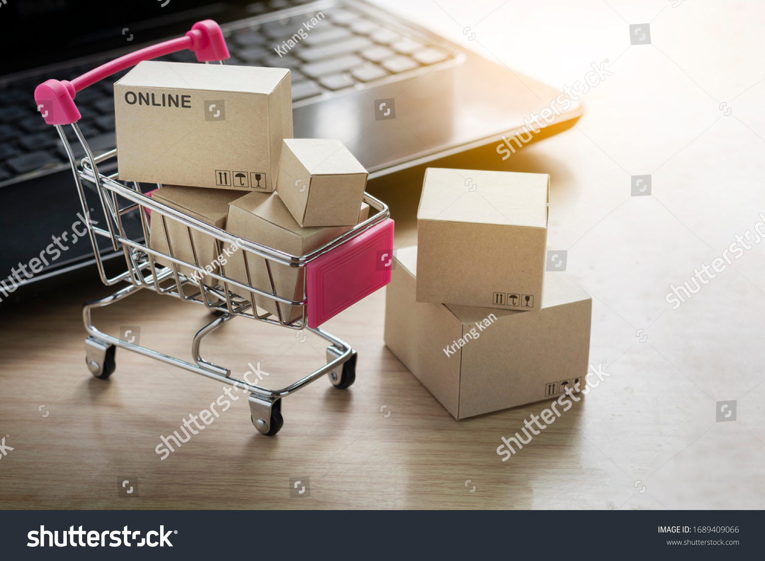 Paper shopping small box express in a shopping cart and laptop notebook on wood table background. Online shopping concept. #1689409066