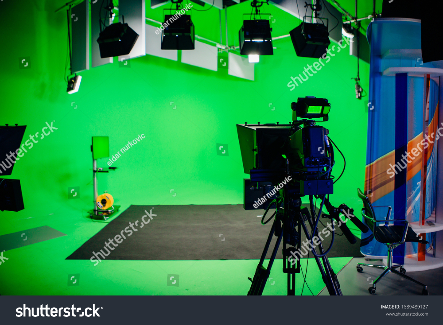 TV Studio recording show.Reportage shooting.TV NEWS program studio with video camera lens and lights.Positioned stage big professional broadcasting camera with headphones.Green key studio #1689489127