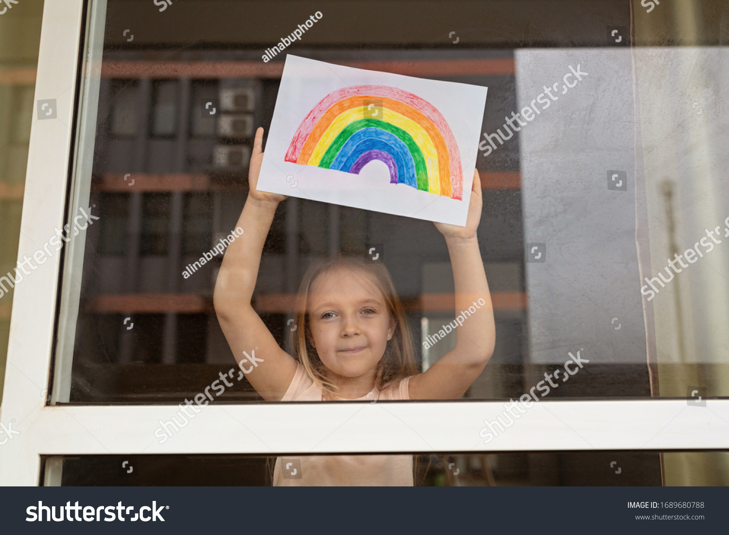 Kid painting rainbow during Covid-19 quarantine at home. Girl near window. Stay at home Social media campaign for coronavirus prevention, let's all be well, hope during coronavirus pandemic concept #1689680788
